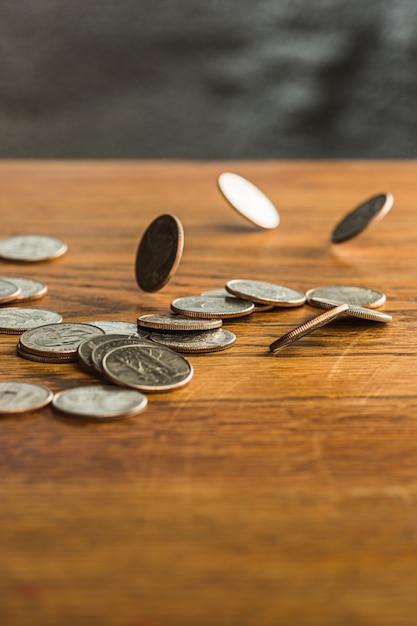 Серебряные и золотые монеты и падающие монеты на деревянном фоне Бесплатные Фотографии