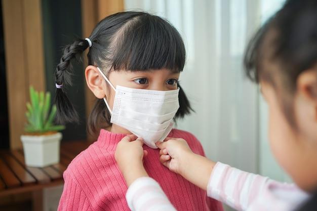 Сестра помогает младшей девушке надеть хирургическую маску. профилактика заражения коронавирусом или инфекцией covid-19 Premium Фотографии