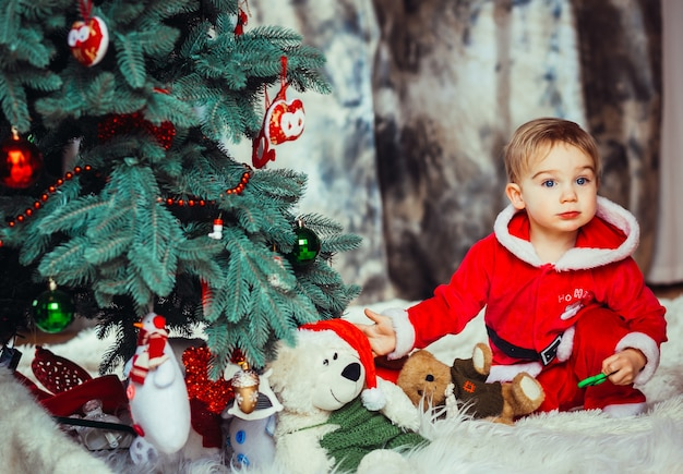 The small child sitting near Christmas tree Free Photo