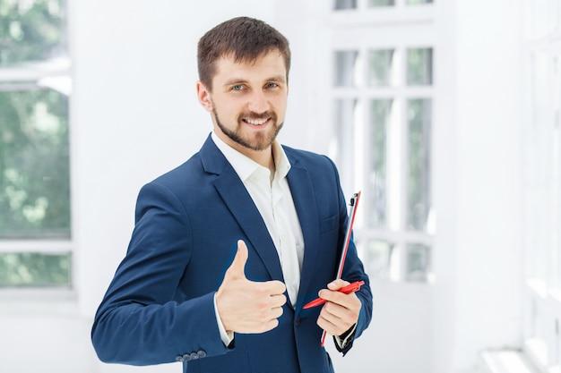 白いオフィスに対して笑顔の男性会社員 無料写真