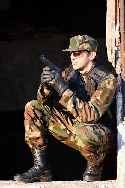 制服を着た兵士は銃を持っています。 Premium写真