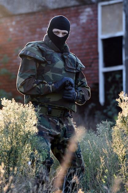 銃を持った兵士は本質的に屋外にいます。 Premium写真