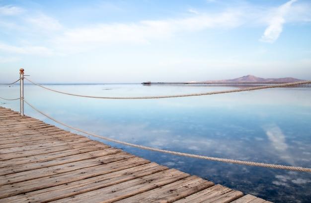 이 공간은 아름다운 긴 목재 부두입니다. 일몰에 근접합니다. 무료 사진