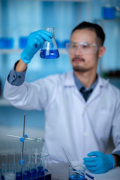 Специальный молодой ученый или исследователь мужского пола, просматривающий химический раствор через пробирку для эксперимента с вакциной, развивающегося в современной биологической лаборатории. Premium Фотографии