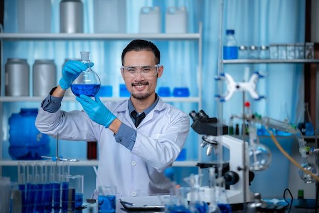 現代の生物学研究所で開発されているワクチン実験のために試験管を通して化学溶液を探している特別な若い男性の科学者または研究者 Premium写真