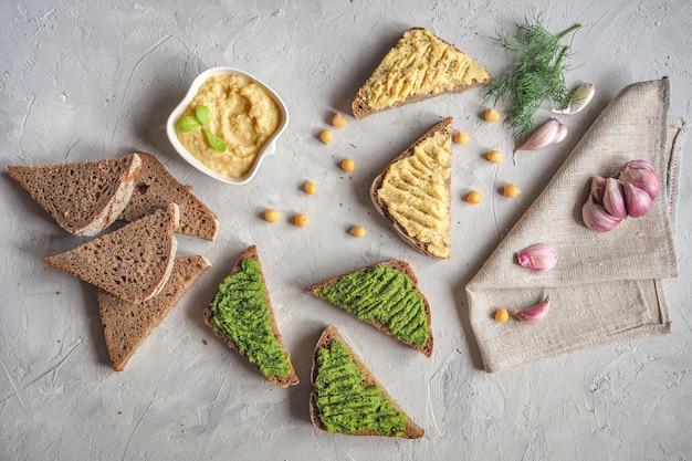 ひよこ豆のパンに広がる。灰色のテーブル、トップビューでさまざまなディップソース Premium写真