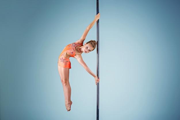 Сильная и грациозная молодая девушка, выполняющая акробатические упражнения на пилоне Бесплатные Фотографии