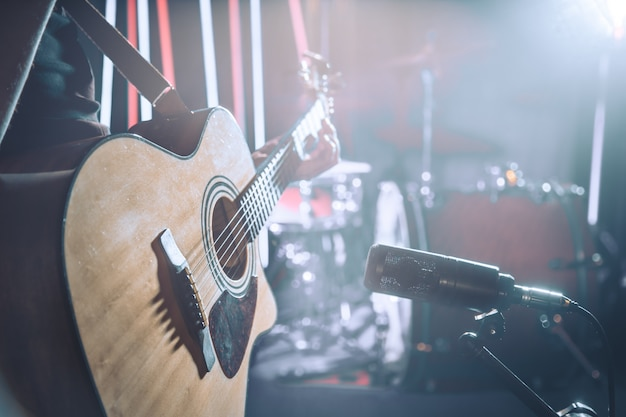 Studioマイクはアコースティックギターのクローズアップを録音します。 Premium写真