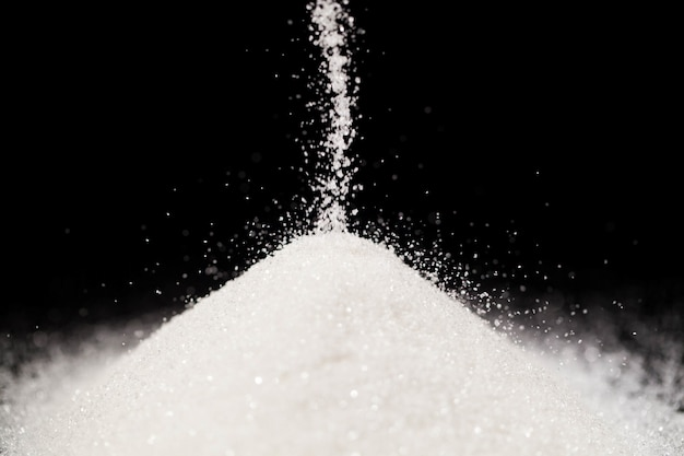 The sugar lies on the black background Free Photo