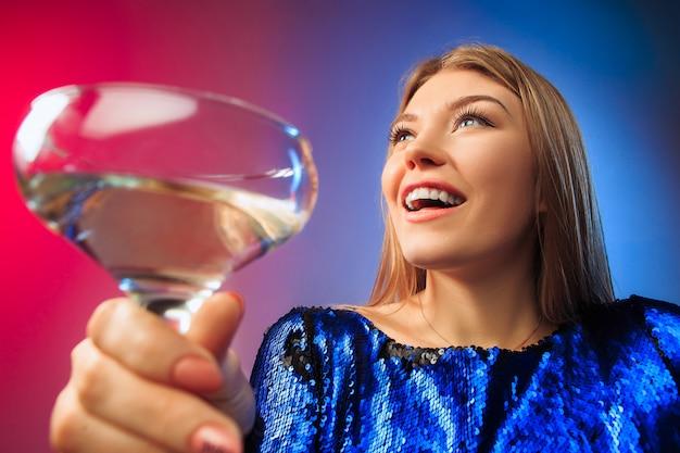 Удивленная молодая женщина в праздничной одежде позирует с бокалом вина Бесплатные Фотографии