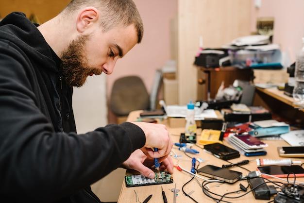 ラボでスマートフォンのマザーボードを修理する技術者。コンピューターハードウェア、携帯電話、電子、修理、アップグレード、技術の概念。ワークショップで電話修理のプロセスを示す男。 Premium写真