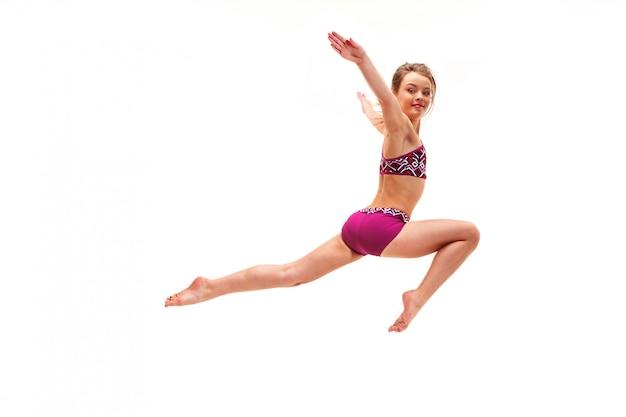 Девушка подросток делает гимнастические упражнения, изолированные на белой стене Бесплатные Фотографии
