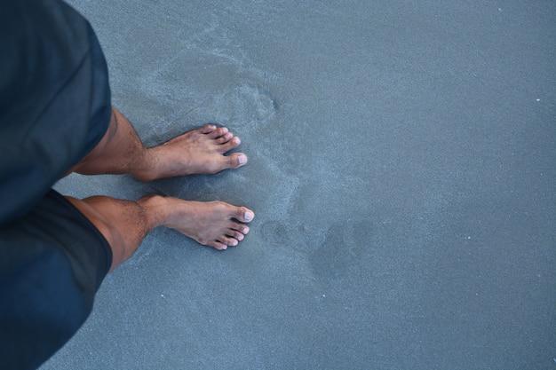 砂の上に靴がない男の足の上 Premium写真