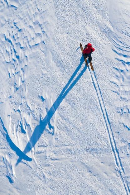 Турист передвигается на лыжах по северному полюсу зимой снимается с коптера сверху Premium Фотографии