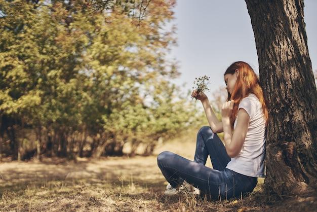여행자는 청바지와 티셔츠를 입은 숲의 야외 나무 근처에 앉아 있습니다. 프리미엄 사진