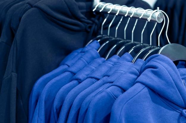 2020年のトレンドカラー。クラシックブルー。衣料品店のハンガーにパーカーをクローズアップ。 Premium写真