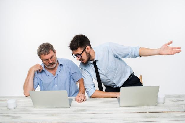 Двое коллег, работающих вместе в офисе на белом фоне. они что-то обсуждают. оба смотрят на один экран компьютера Бесплатные Фотографии