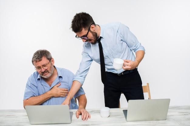 Два коллеги, работающие вместе в офисе на белой стене Бесплатные Фотографии