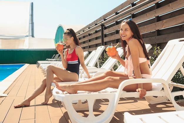 Две девушки играют и отдыхают в бассейне во время летних каникул Бесплатные Фотографии