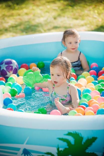 Две маленькие девочки играют с игрушками в надувном бассейне в летний солнечный день Бесплатные Фотографии