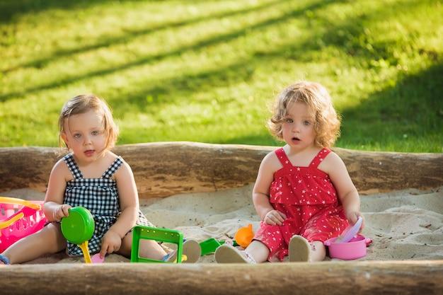 緑の芝生と砂でおもちゃを遊んでいる2人の小さな女の赤ちゃん2歳 無料写真