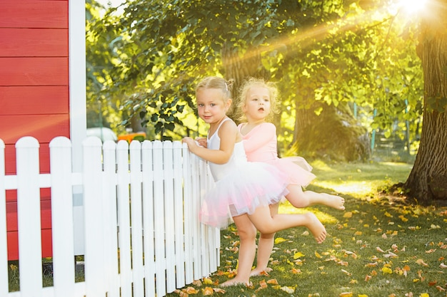 Две маленькие девочки на детской площадке против парка или зеленого леса Бесплатные Фотографии