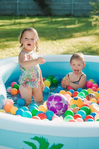 Две двухлетние маленькие девочки играют с игрушками в надувном бассейне в солнечный летний день Бесплатные Фотографии