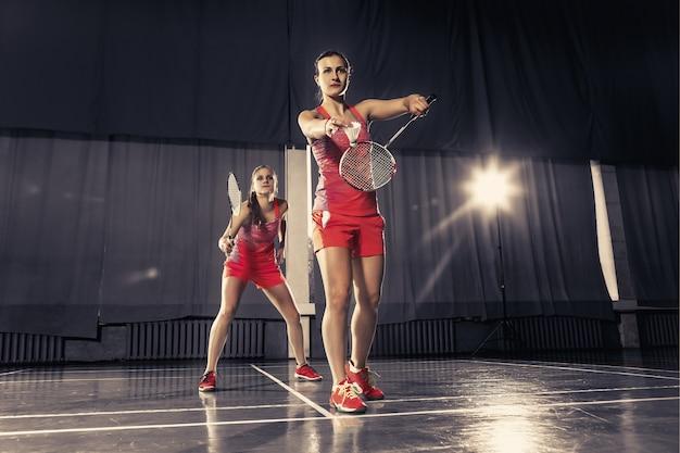 Две молодые женщины играют в бадминтон над тренажерным залом. концептуальная игра в паре Бесплатные Фотографии