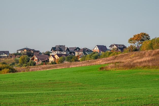 녹색 속이 빈 마을. 그린 필드에서 현대 오두막 마을입니다. 러시아. 프리미엄 사진