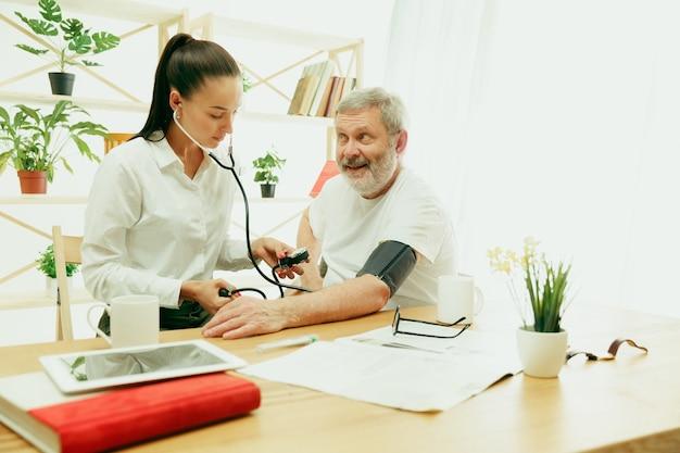 年配の男性の世話をしている訪問看護師またはヘルスビジター。自宅でのライフスタイルの肖像画。医学、ヘルスケアおよび予防。訪問中に患者の血圧をチェックまたは測定する女の子。 無料写真