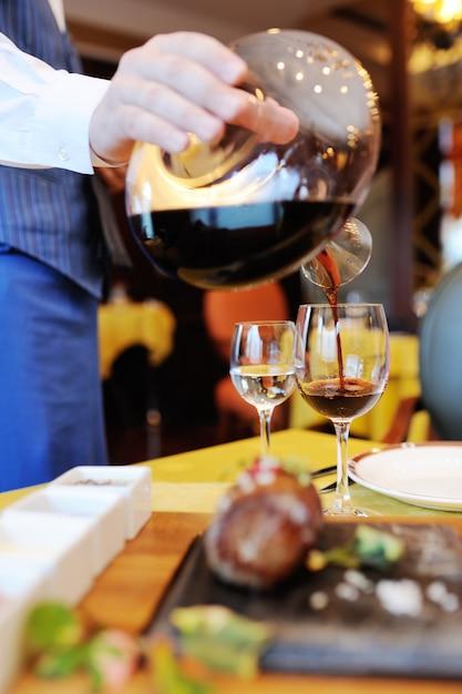 Официант наливает красное вино из красивой бутылки на фоне ресторана и еды Premium Фотографии
