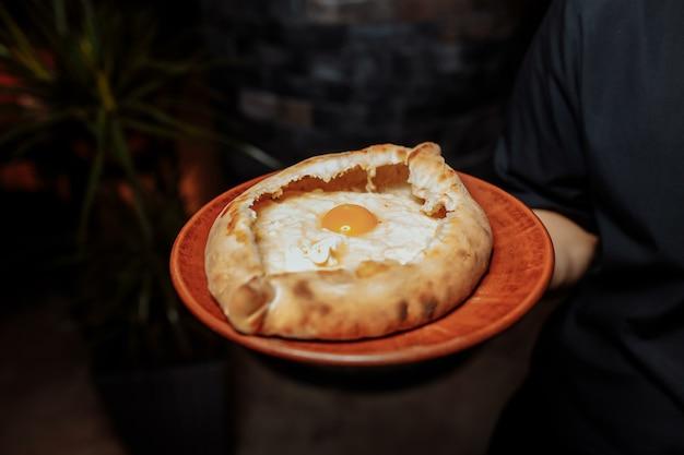 黒い手袋をしたウェイターの手は、チーズと卵を添えた2つの伝統的なハチャプリを持っています。 Premium写真