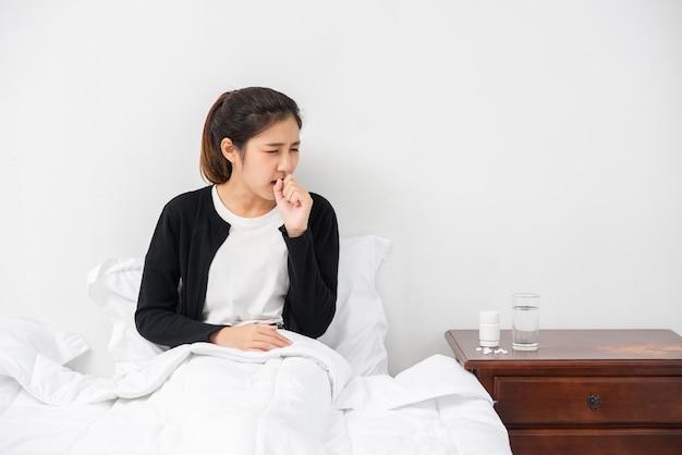 女性は咳をして口を手で覆い、ベッドに座った。 無料写真