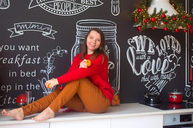 Женщина в красном сидит на кухне и готовит рождественский ужин. Premium Фотографии