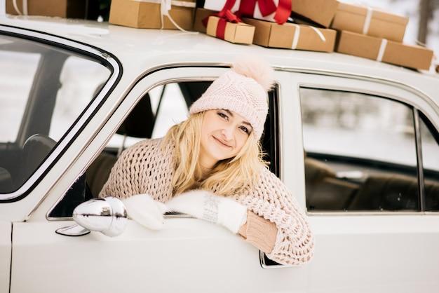 女性は、クリスマスツリーで飾られたレトロな車に乗って、雪に覆われた森の中でプレゼントをします。冬のクリスマスのコンセプト Premium写真