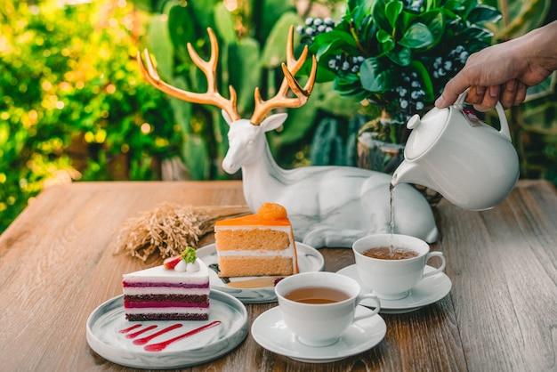女性の手は、朝の熱いお茶とケーキを注いでいます。 Premium写真