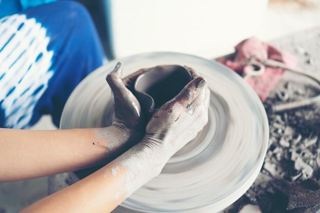 Руки женщины крупным планом, мастерская студия керамики работает с глиной на гончарном круге Premium Фотографии