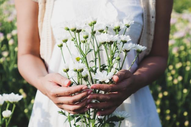 Женщина стояла, держа в цветочном саду много белых цветов хризантемы. Premium Фотографии