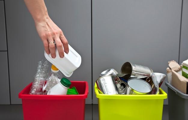 女性はゴミを分別するためにプラスチック容器を4つの容器の1つに投げます Premium写真