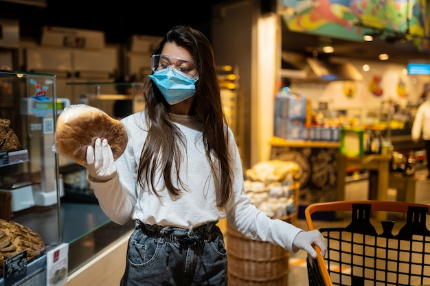 サージカルマスクをした女性がパンを買う 無料写真