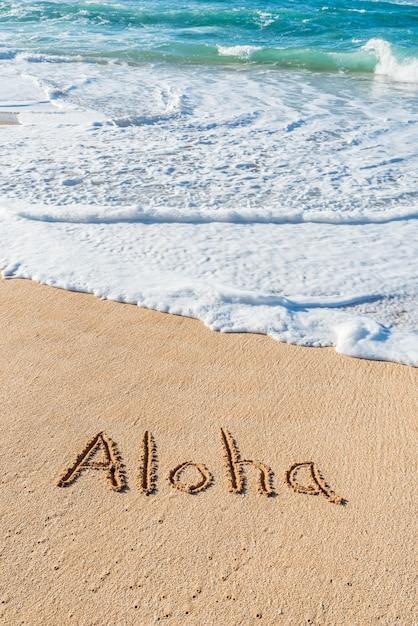 波を洗ってビーチの砂に書かれたアロハという言葉 Premium写真