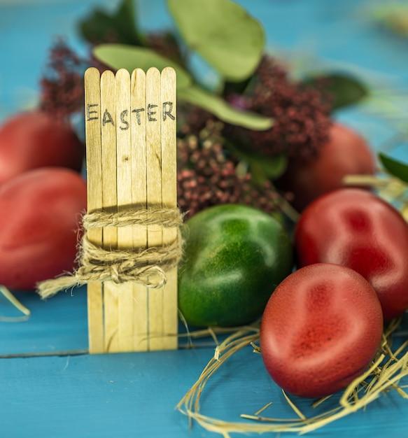 木の棒、緑と美しいお祝い卵の概念ブロックテキストの単語イースター 無料写真