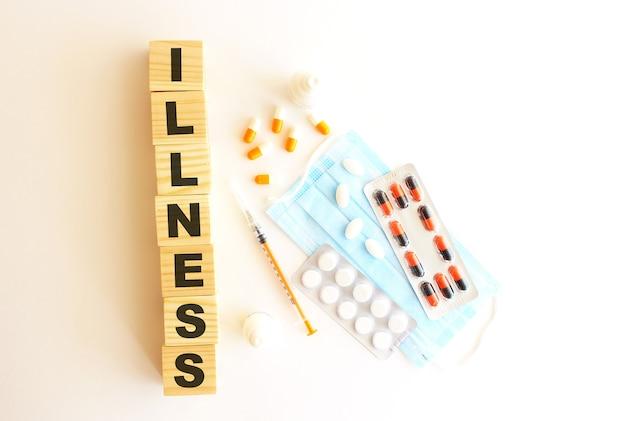 Слово болезнь состоит из деревянных кубиков на белом фоне с лекарствами и медицинской маской. Premium Фотографии