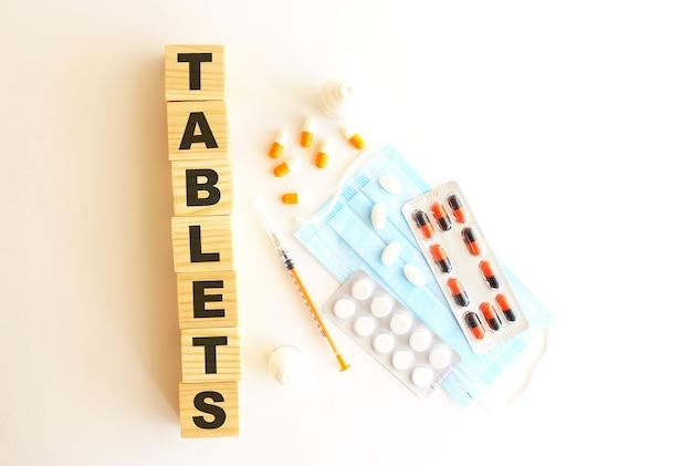 Слово таблетки состоит из деревянных кубиков на белом фоне с медицинскими препаратами и медицинской маской. Premium Фотографии