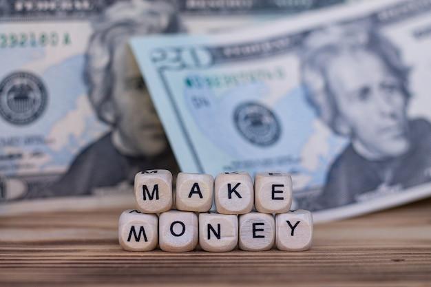 Слова зарабатывать деньги, выложенные буквами на деревянных кубиках на фоне долларовых купюр. Premium Фотографии