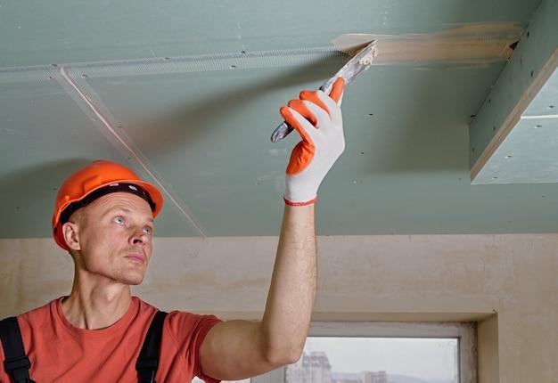 Рабочий заполняет швы гипсокартона гипсовой шпатлевкой. Premium Фотографии