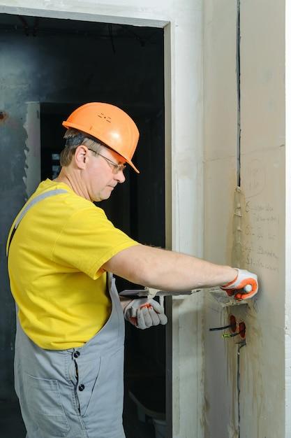 Рабочий держит мастерки с гипсом. он закрывает электрические гофрированные трубы в стене. Premium Фотографии