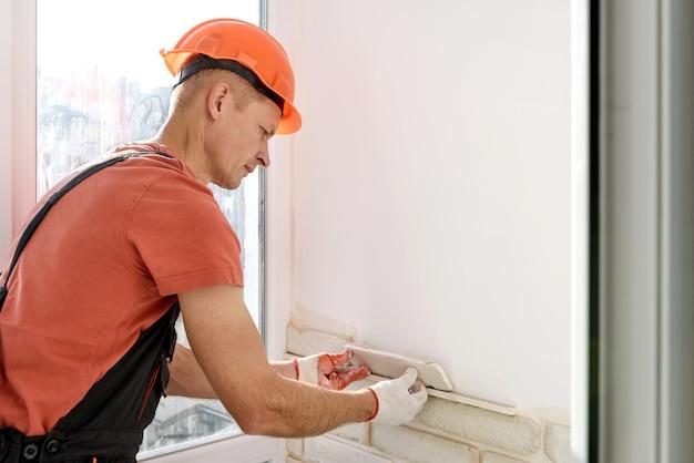 Рабочий кладет на стену гипсовую плитку. Premium Фотографии