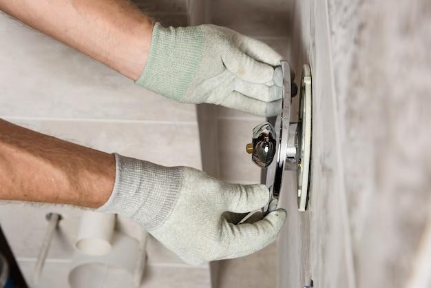 Руки рабочего монтируют встраиваемый кран. Premium Фотографии
