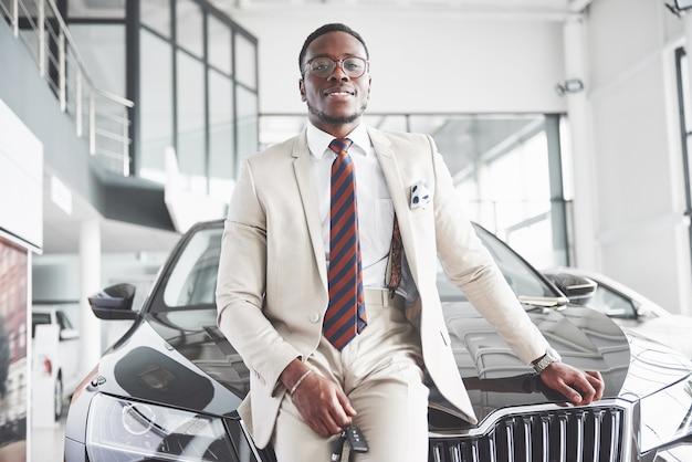 若い魅力的な黒人実業家が新しい車を購入すると、夢が叶います。 無料写真